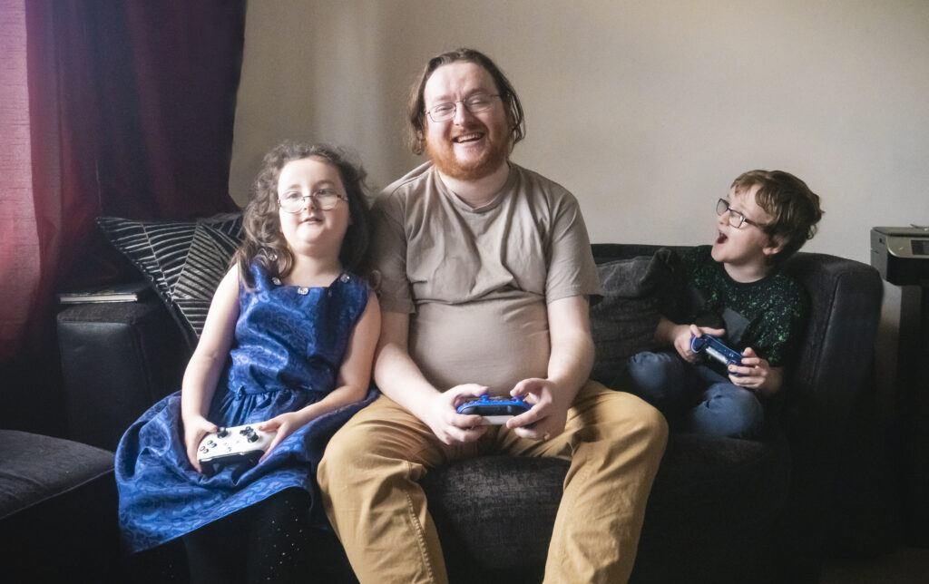 A photo of Jonathan and his two young children, one girl one boy each holding an Xbox controller grinning at each other!